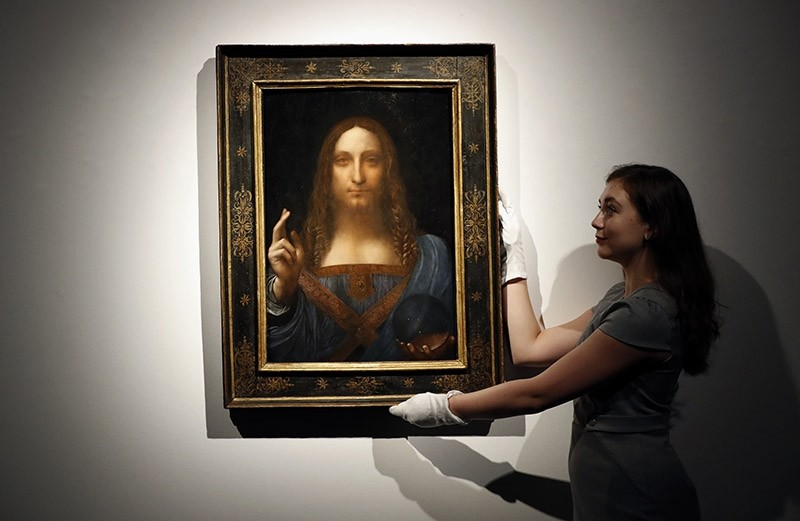 In this Oct. 24, 2017 file photo, an employee poses with Leonardo da Vinci's ,Salvator Mundi, on display at Christie's auction rooms in London. (AP Photo)