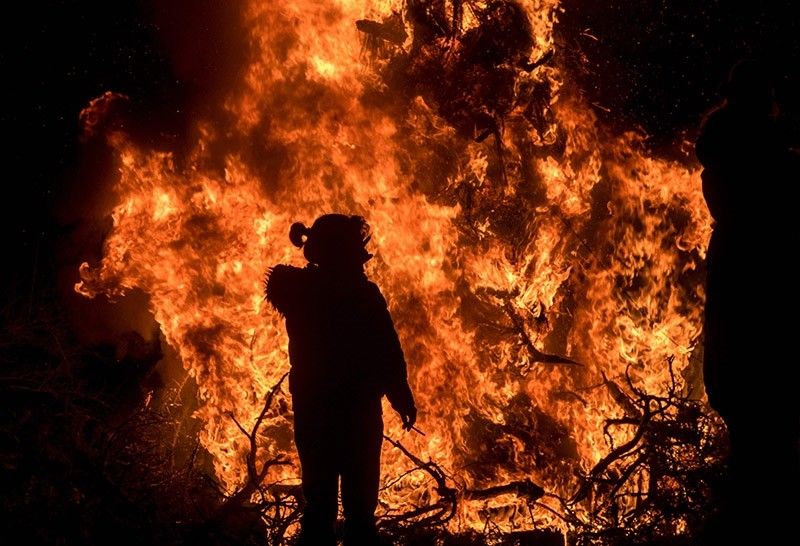 A Bulgarian reveller looks at a ritual bonfire near the village of Dobrinishte on February 26, 2017. (AFP Photo)