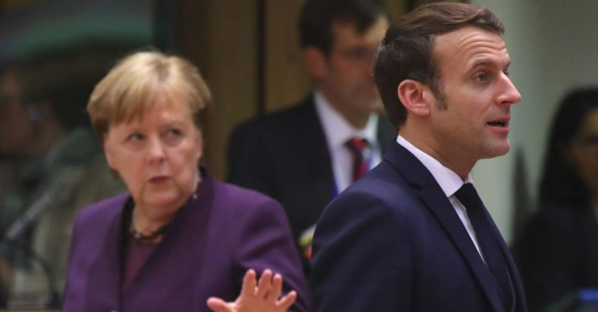 French President Emmanuel Macron and German Chancellor Angela Merkel arrives for a round table meeting at an EU summit, Brussels, Feb. 20, 2020. (AP Photo)