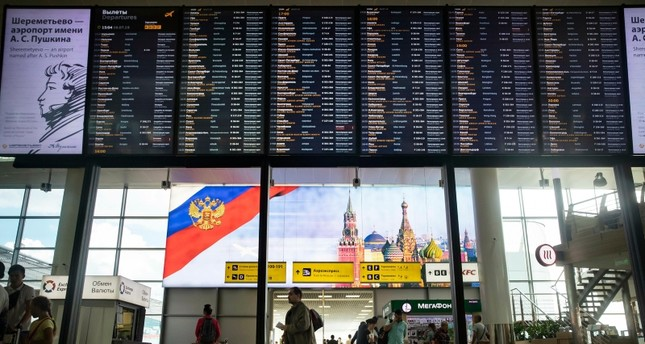 Passengers walk past a departure board at Sheremetyevo international airport in Moscow, Russia, Monday, July 8, 2019. (AP Photo)