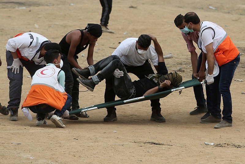 A demonstrator is evacuated after inhaling tear gas fired by Israeli troops at a protest where Palestinians demand the right to return to their homeland, at the Israel-Gaza border in the southern Gaza Strip, May 4, 2018. (Reuters Photo)