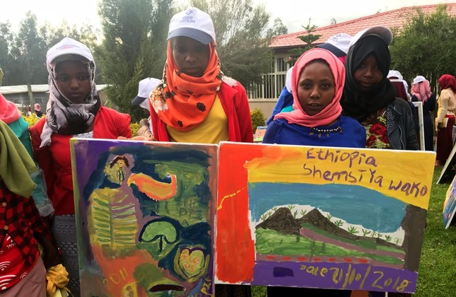 Ethiophian children show the paintings they did.