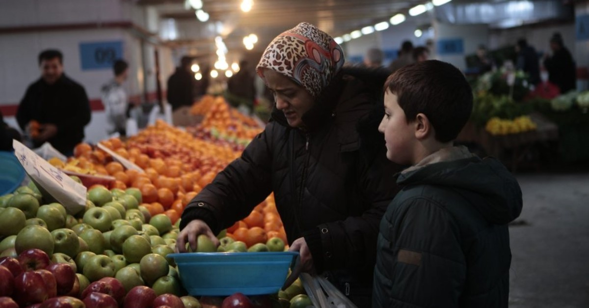 A Turkish woman, accompanied by her son, picks up fruit at a stall in a neighborhood marketplace in Turkey.