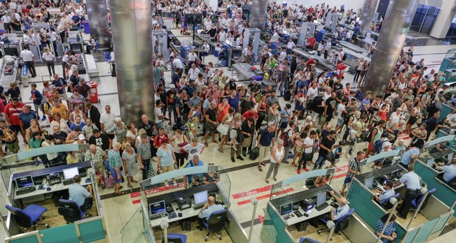 People wait in line for the security and passport control at Antalya International Airport, Turkey on Aug. 10.