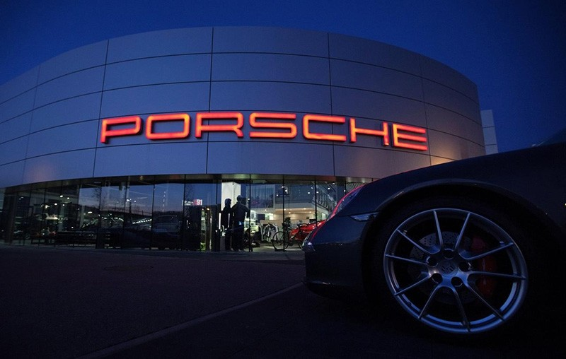 An illuminated Porsche logo is pictured on a building of a Porsche retail centre in Niederwangen, Switzerland, March 9, 2012. (Reuters Photo)