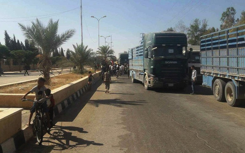 A handout picture released by the Syrian Arab News Agency (SANA) shows trucks carrying food aid arriving in Deir Ez-Zor on September 7, 2017 (AFP Photo)