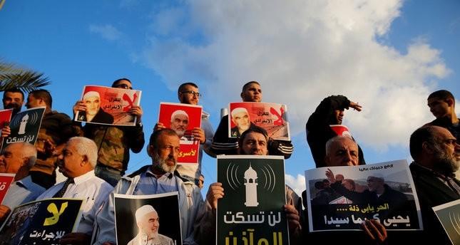 مجموعة من الفلسطينيين يتظاهرون ضد قانون حظر الآذان عبر مكبرات الصوت   (رويترز)