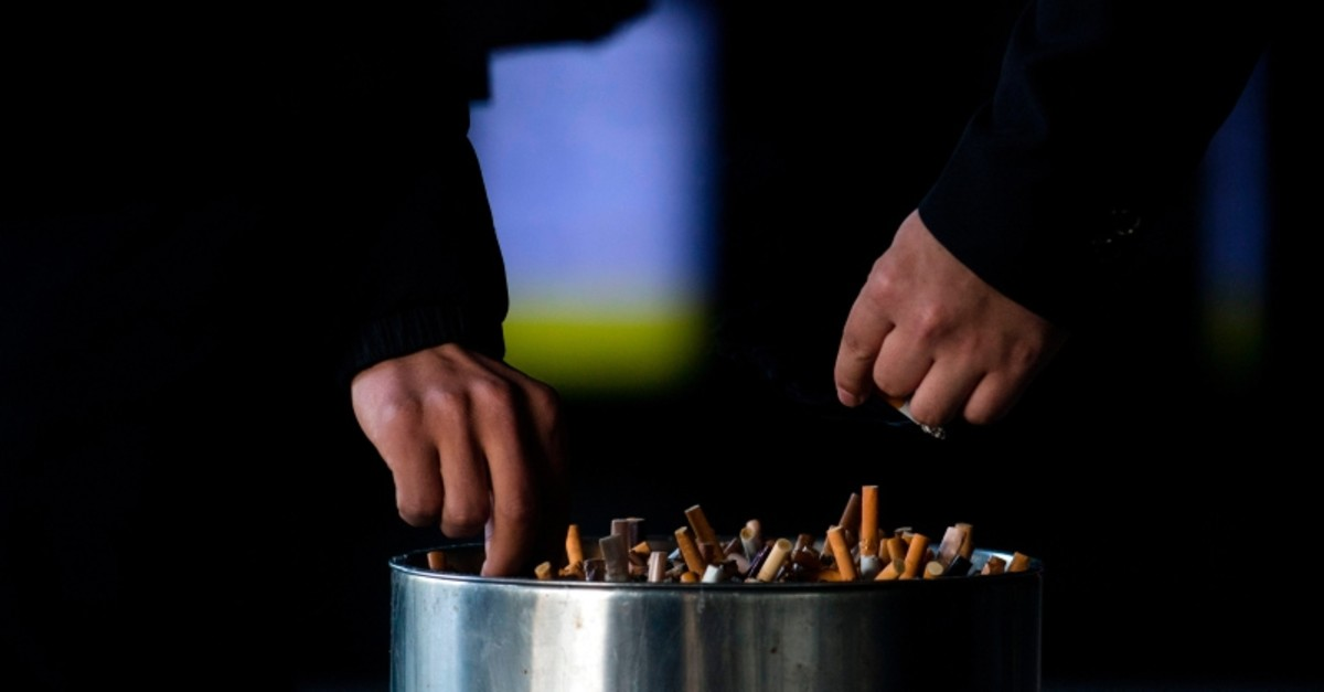 This file photo taken on February 28, 2017 shows a man putting out his cigarette in an ashtray at a railway station in Shanghai (AFP Photo)