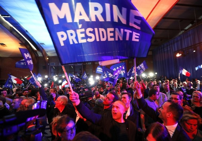 Supporters of French presidential election candidate for the far-right National Front party, Le Pen (unseen) celebrating after the results of the first round of the elections at her party's headquarters in Henin-Beaumont, Northern France, April 23.