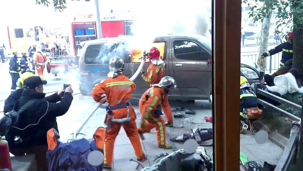 In this image taken from cellphone video provided to the Associated Press, firefighters put out a blaze after a minivan carrying gas tanks plowed into pedestrians along a street in Shanghai, Feb. 2, 2018. (AP Photo)