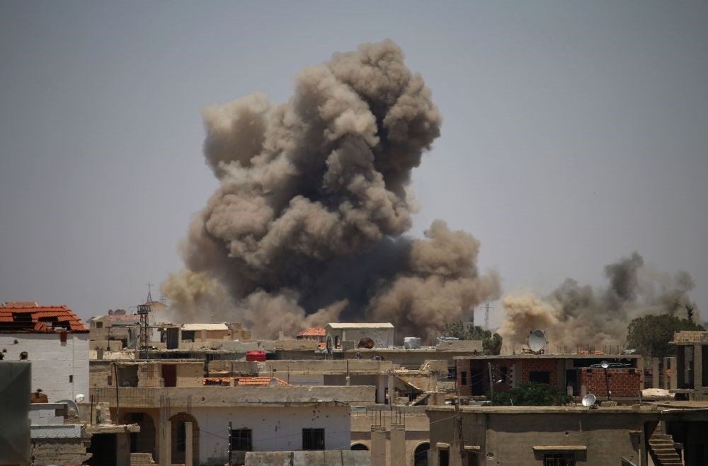 Smoke rises above buildings during an airstrike by Syrian regime forces on the town of Busra al-Harir in the eastern province of Daraa, June 24.