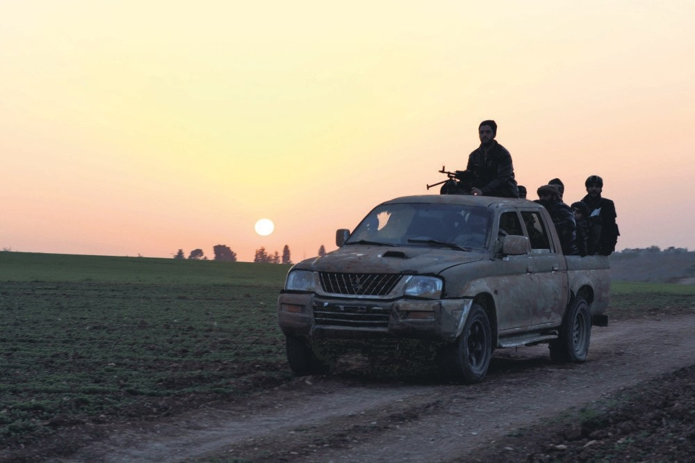Opposition members head towards the village of Al-Khuwayn during battles with regime forces in Idlib, Jan. 13.