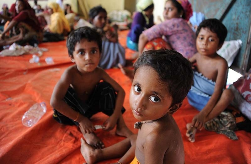 A group of rescued migrant children, mostly Rohingya from Myanmar and Bangladesh, sit upon their arrival at the new confinement area in the fishing town of Kuala Langsa in Aceh province on May 15, 2015 (AFP File Photo)