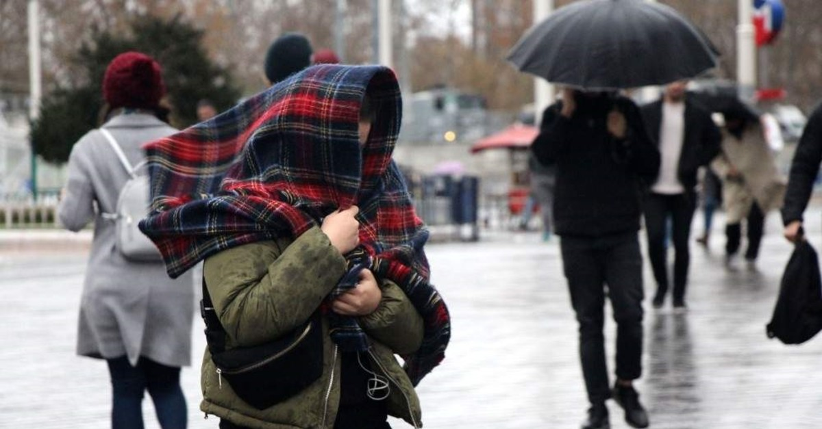 Heavy southwesterly winds and rainfall hit Istanbul as people struggle to walk around Taksim Square, Dec. 23, 2019. (DHA Photo)