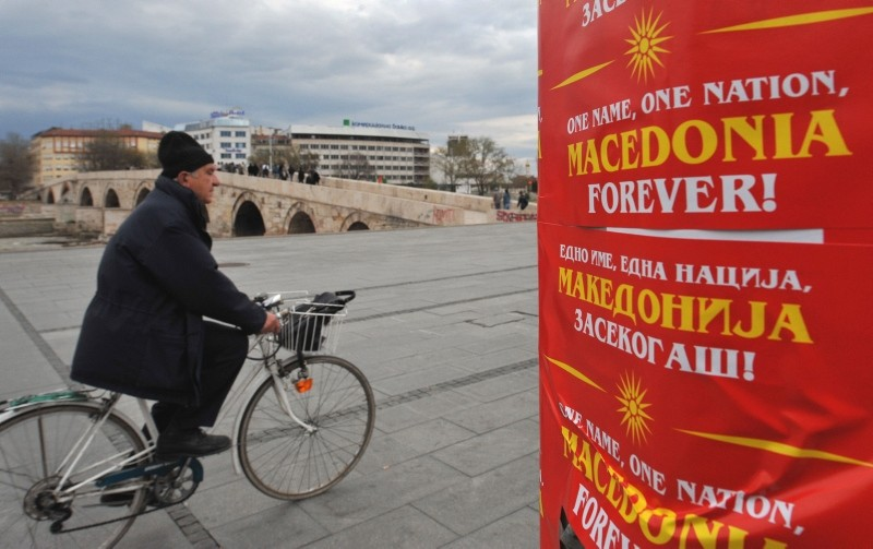 This March 27, 2008 file photo shows a man passing by a panel with placards, saying ,One name, one nation, Macedonia forever, and adorned with the original flag of the Republic of Macedonia in Skopje, Macedonia. (AFP Photo)
