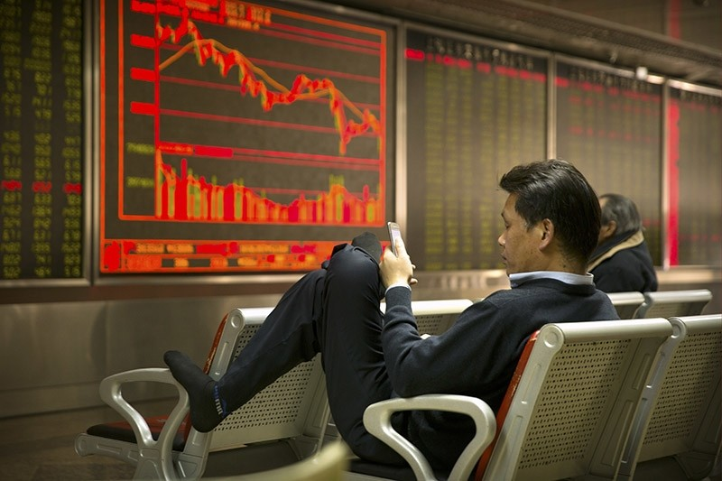 A Chinese investor uses his smartphone as he monitors stock prices at a brokerage house in Beijing, Friday, March 23, 2018. (AP Photo)