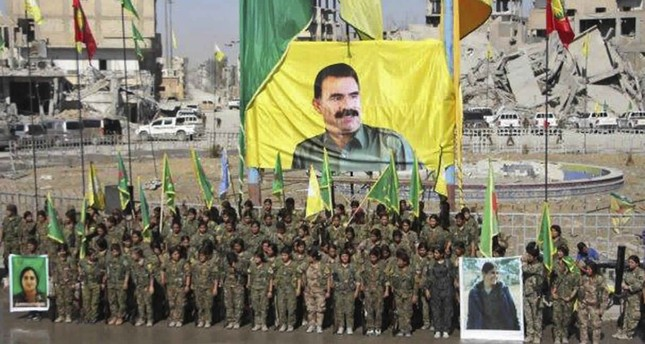 YPG members stand under a portrait of their PKK Abdullah Ocalan, as they celebrate victory against Daesh in Raqqa, Syria.(Ronahi TV, via AP)
