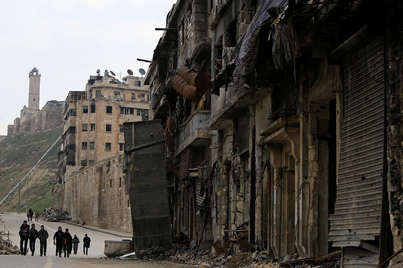 People walk past damaged shops in the Old City of Aleppo, Syria January 31, 2017. (Reuters Photo)