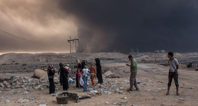 Iraqi villagers gather on a road as smoke rises from the Qayyarah area, southern Mosul, Oct. 19, 2016, during an operation against Daesh terrorists to retake the main hub city.
