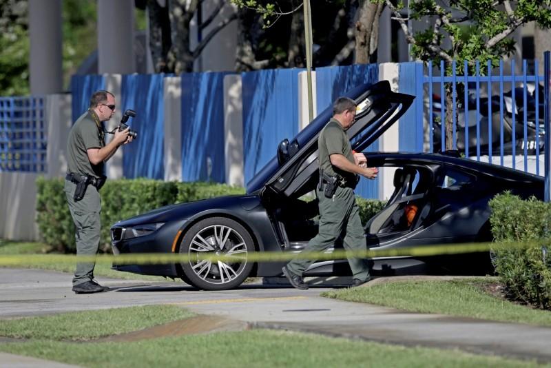 Investigators surround a vehicle after rapper XXXTentacion was shot in Deerfield Beach, Fla. (AP Photo)