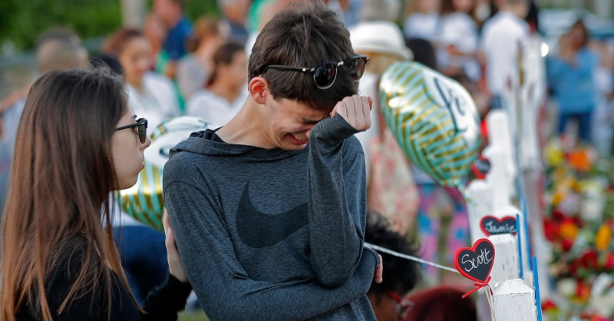 Daniel Bishop, 16, a student at Marjory Stoneman Douglas High School, cries at a makeshift memorial outside the school, in Parkland, Fla., Sunday, Feb. 18, 2018. (AP Photo)