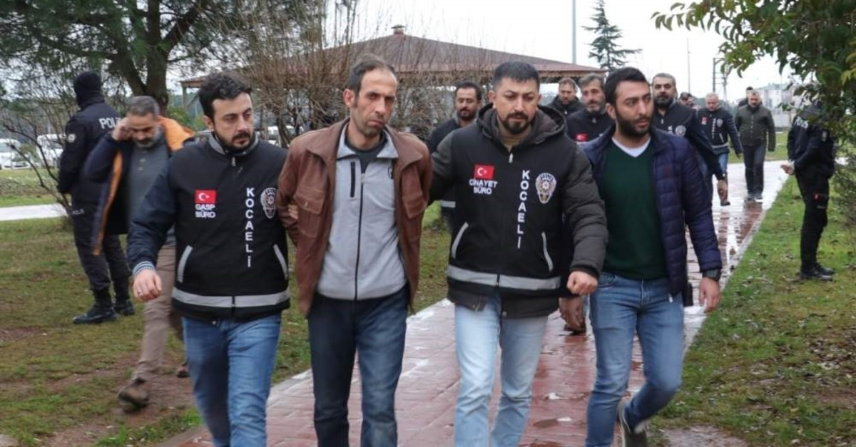Police officers escort Tuncer Ustael to the courthouse in Kocaeli in this undated photo. (?HA Photo)