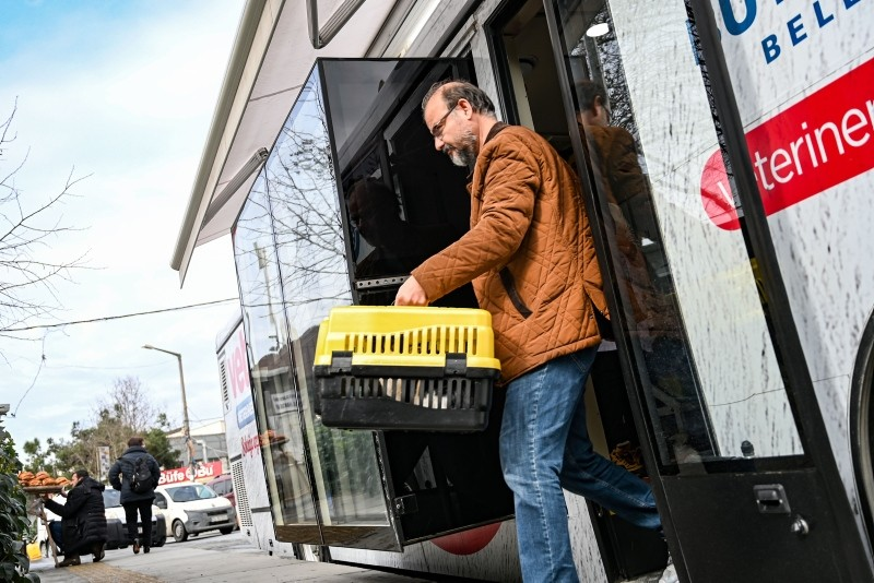 A man takes a stray cat inside a box from the Vetbus after a check up on January 31, 2019 at Rumelihisari district in northern Istanbul.