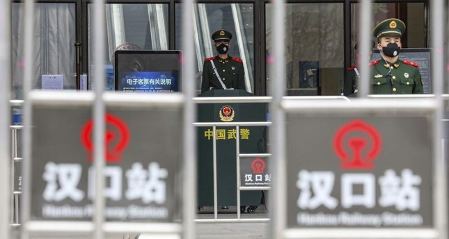 In this Thursday, Jan. 23, 2020, file photo, Chinese paramilitary police stand guard outside the closed Hankou Railway Station in Wuhan in central China's Hubei Province. Chinatopix via AP
