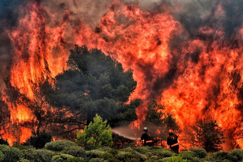 Firefighters try to extinguish flames during a wildfire at the village of Kineta, near Athens, on July 24, 2018. (AFP Photo)