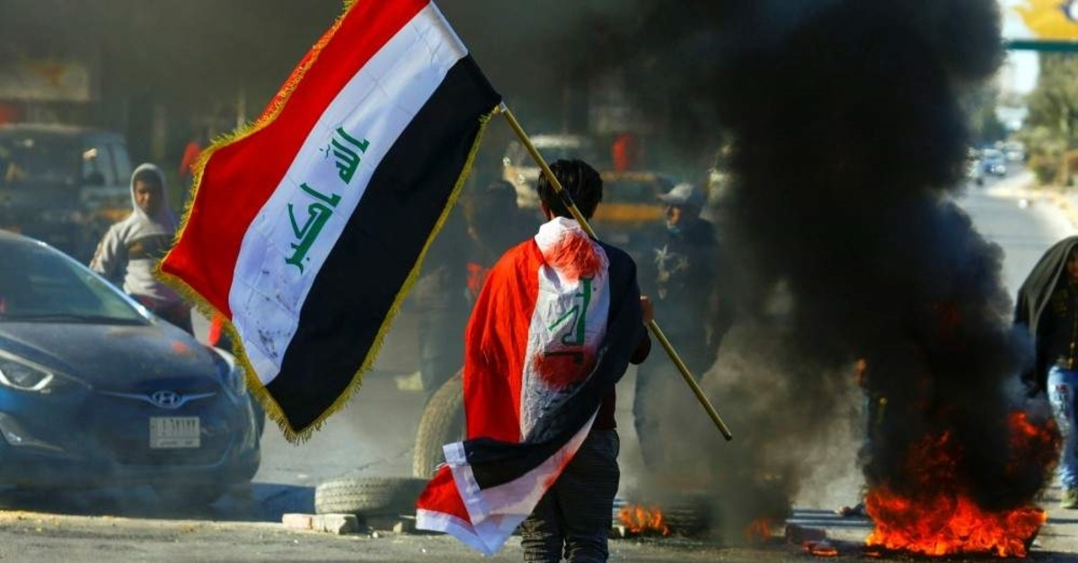 A demonstrator carries an Iraqi flag as he walks near burning tires during ongoing anti-government protests, Najaf, Jan. 12, 2020. (Reuters Photo)