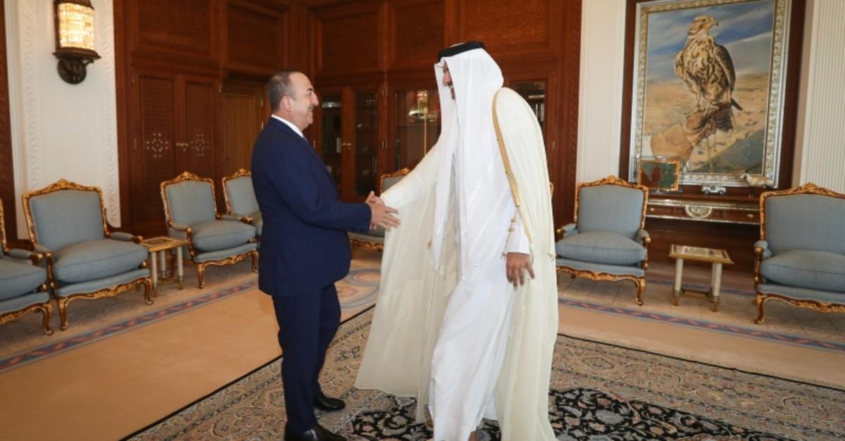 Qatari Emir Sheikh Tamim bin Hamad Al-Thani shakes hands with Turkish Foreign Minister Mevlu00fct u00c7avuu015fou011flu before a meeting in Doha, Nov. 4, 2019. (AA Photo)