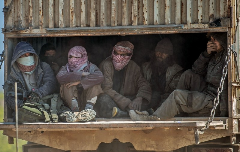In this Feb. 20, 2019 photo, a truck carrying men, identified as Daesh fighters who surrendered to the U.S.-backedu00a0SDF,u00a0consisting mainly for PKK-affiliated YPG terrorists, transports them out of Baghouz in Deir el-Zour province, Syria. (AFP Photo)