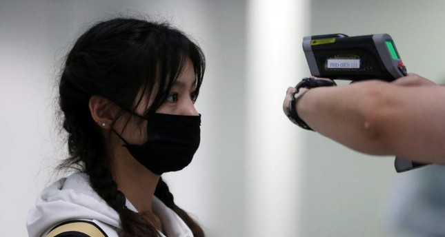 A passenger gets her temperature checked by a worker using an infrared thermometer amid coronavirus outbreak, at Hong Kong International Airport, Feb. 7, 2020. Reuters Photo