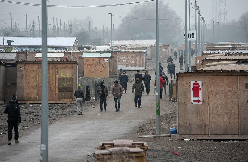 This file photo taken on January 25, 2017 shows migrants walking inside the migrants camp of Grande-Synthe in Grande-Synthe, near Dunkerque, northern France. (AFP Photo)