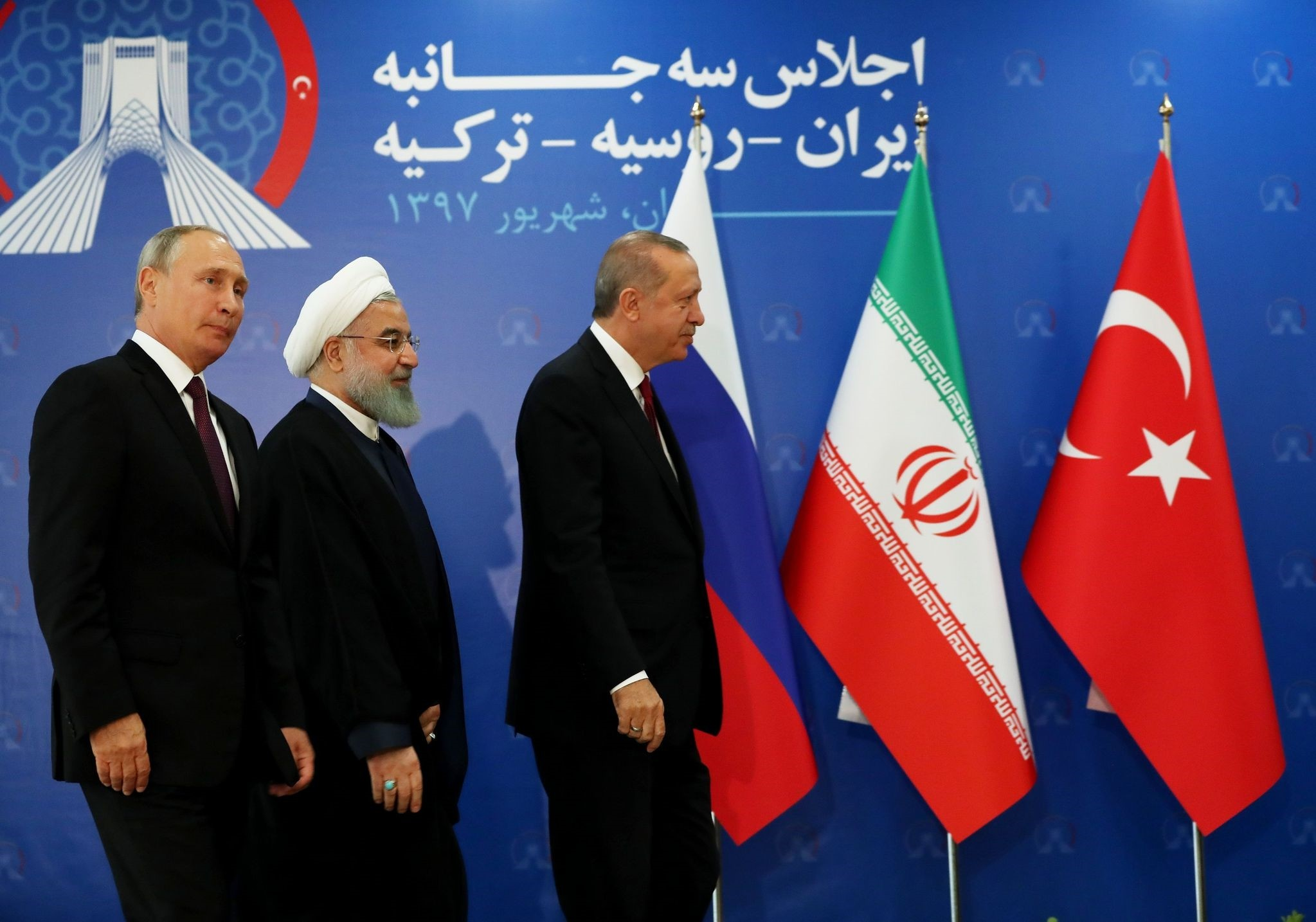 President Recep Tayyip Erdou011fan (R), Iranian President Hassan Rouhani (C) and Russian President Vladimir Putin (L) prepare to leave the stage during the trilateral summit on the Idlib crisis, Tehran, Sept. 7.