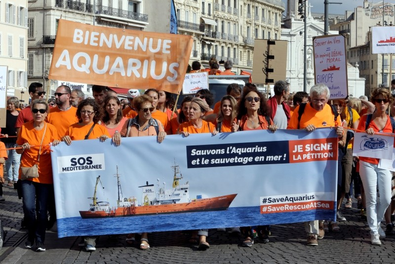 People gather to support the Aquarius ship that rescues migrants operated by the humanitarian group SOS Mediterranee, in the Old-Port of Marseille, southern France, Saturday, Oct. 6, 2018. (AP Photo)