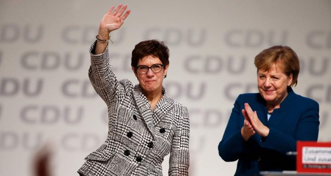 Annegret Kramp-Karrenbauer, the newly elected secretary-general of Germany's conservative Christian Democratic Union (CDU), greets supporters with German Chancellor Angela Merkel (R) during the CDU congress in Hamburg, Dec. 7.