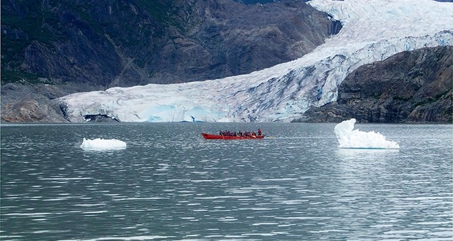 Kayakers paddle on Mendenhall Lake, with Mendenhall Glacier in the background and icebergs in the foreground, on Friday, Aug. 11, 2017 (AP Photo)