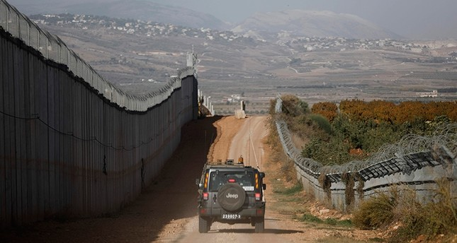 An Israeli army vehicles driving along the border fence between Lebanon (L) and Israel, near Metula, Israel, Nov. 16, 2017. (AFP Photo)