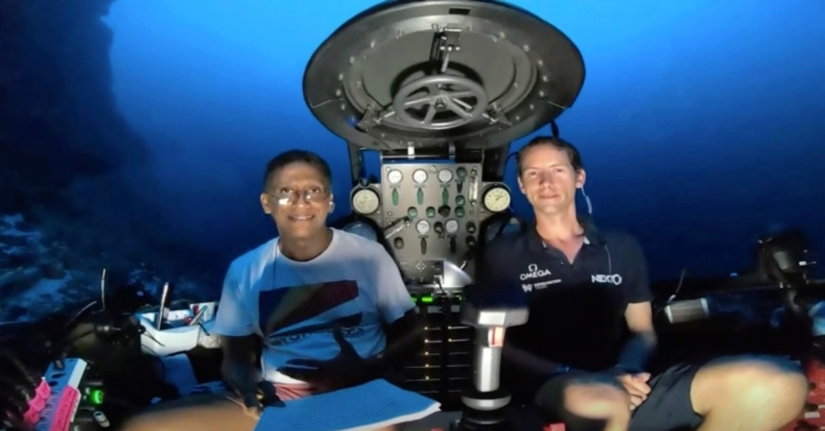 An image taken from video issued by Nekton shows Seychelles President Danny Faure, left, after speaking from inside a submersible from the vessel Ocean Zephyr, under the water off the coast of Desroches, Seychelles, April 14, 2019. (AP Photo)