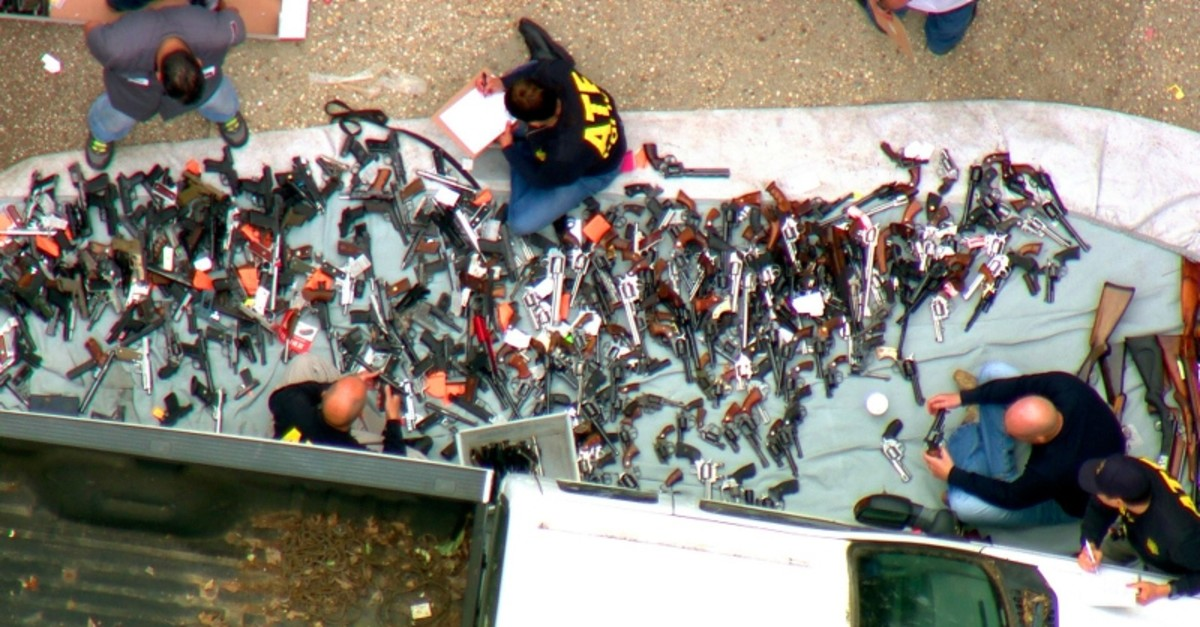 This photo from video provided by KCBS/KCAL-TV shows investigators from the U.S. Bureau of Alcohol, Tobacco, Firearms and Explosives and the police inspecting a large cache of weapons seized at a home in the affluent Holmby Hills area of Los Angeles