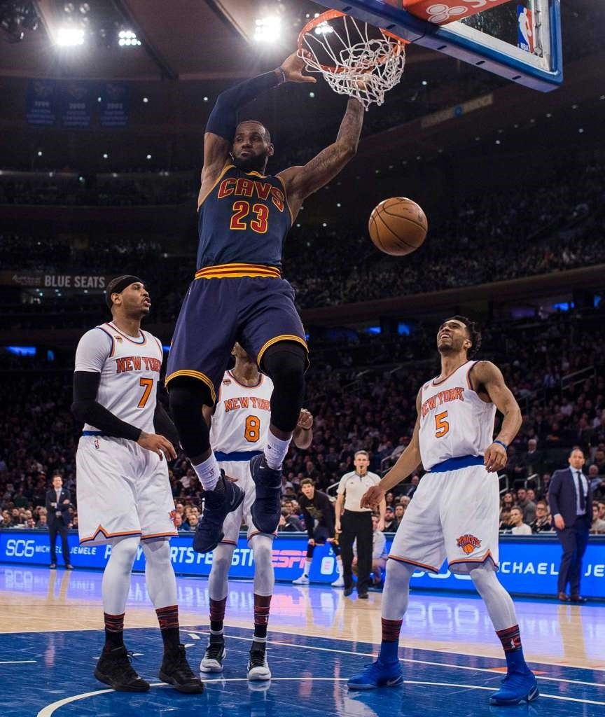Cleveland Cavaliersu2019 LeBron James (23) dunks in front of New York Knicksu2019  Courtney Lee (5) and Justin Holiday (8) during the first half of an NBA basketball game.