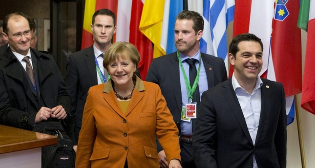 Greek Prime Minister Alexis Tsipras, right, walks with German Chancellor Angela Merkel, center, as they leave an EU summit in Brussels.