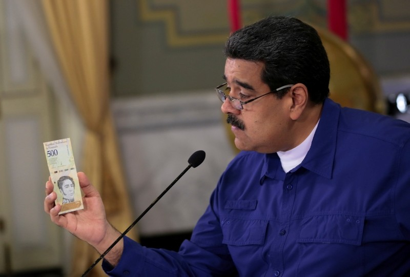 Venezuela's President Nicolas Maduro holds a bank note of the new currency Bolivar Soberano (Sovereign Bolivar) as he speaks during a meeting with ministers at Miraflores Palace in Caracas, Venezuela July 25, 2018. (Miraflores Palace via Reuters)