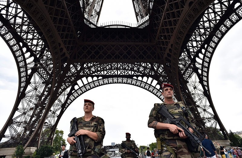 This file photo taken on July 20, 2016 shows armed French soldiers of the 35th RAP (35e regiment d'artillerie parachutiste), part of Operation Sentinelle, patroling under at the Eiffel Tower in Paris. (AFP Photo)
