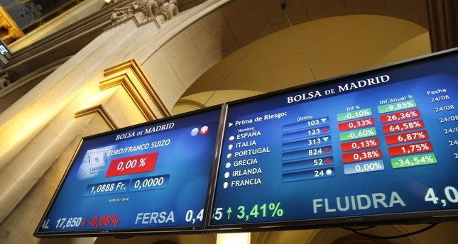 Screens displaying the price of the euro against the Swiss Franc (L) and another showing several European risk premium figures at Madrid's Stock Exchange in Madrid, Spain, on Aug. 24.