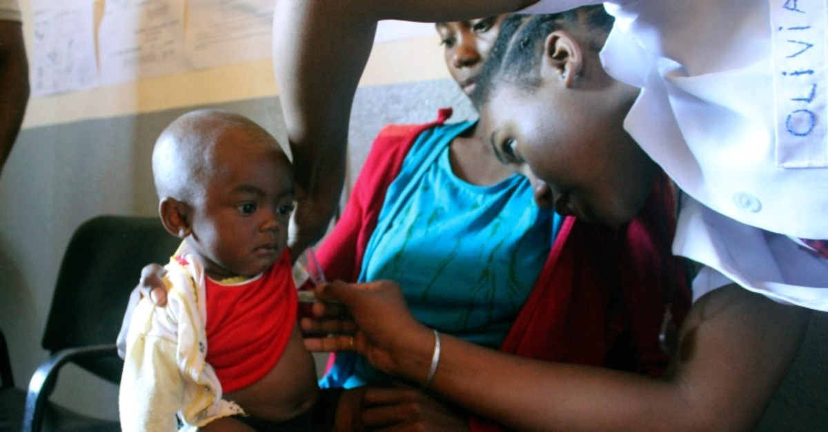 In this photo taken on Thursday, March 21, 2019, a volunteer nurse examines 6-moth-old Sarobidy, who is infected with measles, while her mother Nifaliana Razaijafisoa looks on, at a healthcare centre in Larintsena, Madagascar. (AP Photo)