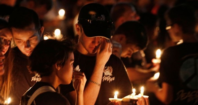 Thousands of mourners hold candles at a vigil for victims at the Marjory Stoneman Douglas High School, Parkland, Florida, Feb. 15, 2018.