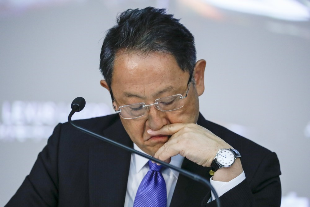 Akio Toyoda, President of Toyota Motor Corp., looks at his files during a press conference announcing the company's financial results.