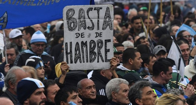 A protester holds a placard reading No More Hunger during a demonstration against the government of Argentine President Mauricio Macri.